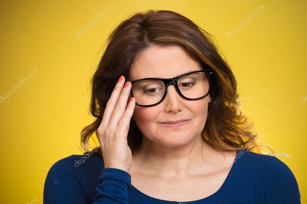 Mature, shy, sad woman playing nervously with glasses