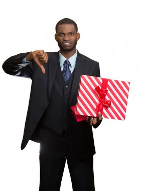 Upset man holding gift box displeased, showing thumbs down