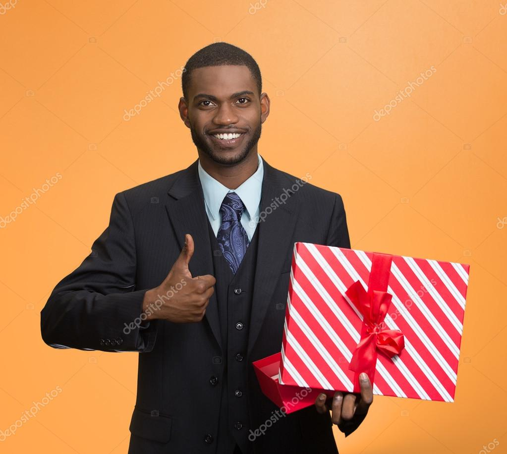 Smiling business man holding present, giving thumb up