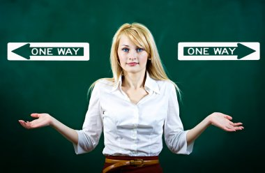Confused young woman shrugs shoulders, uncertain which way to go in life