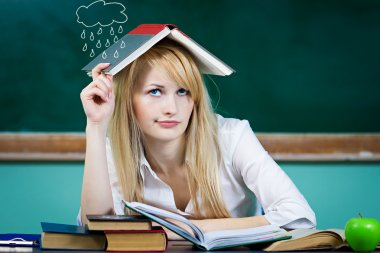 Student, teacher, sitting at desk in classroom, looking upwards confused