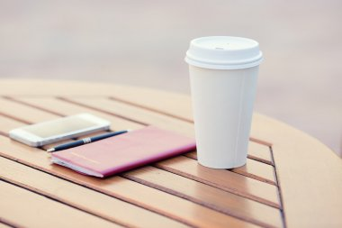 Closeup coffee cup, weekly organizer, smartphone, pen on table of city cafe