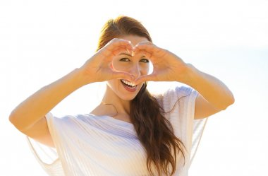 Beautiful woman shows heart shape hands on summer sunny day, oceanside background