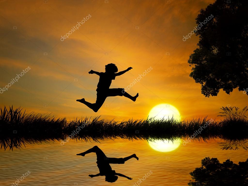 Happy boy, teenager jumping in water, over lake with sunset background