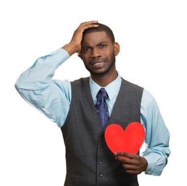 Heartbroken man, holding red heart in hand