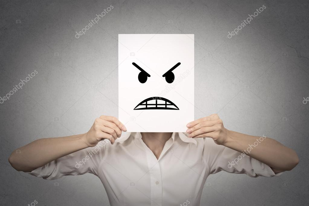 Businesswoman covering her face with angry mask