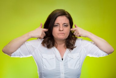 Woman plugging ears annoyed by loud noise ignoring someone