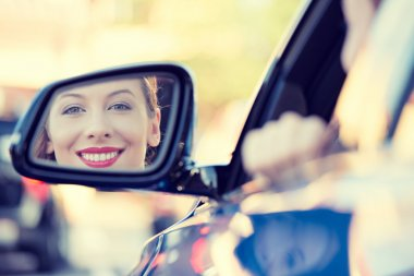 Woman driver looking in car side view mirror