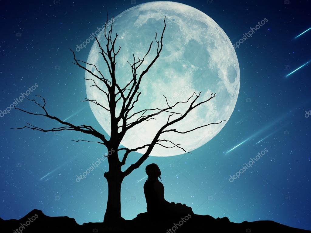 Silhouette of a meditating man on moonlight sky background