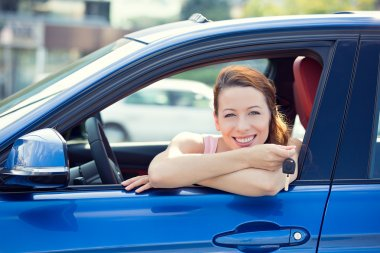 woman, buyer sitting in her new car showing keys