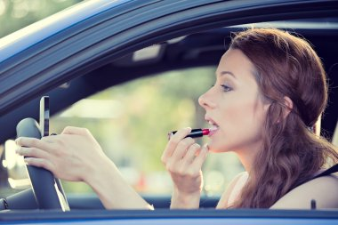 young woman applying makeup while driving car