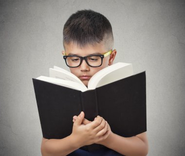 child with glasses reading book