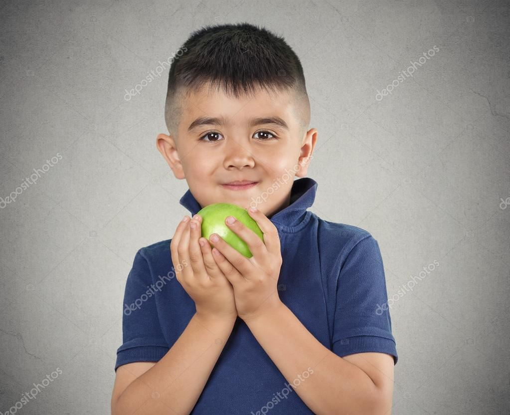 Happy child boy eating green apple
