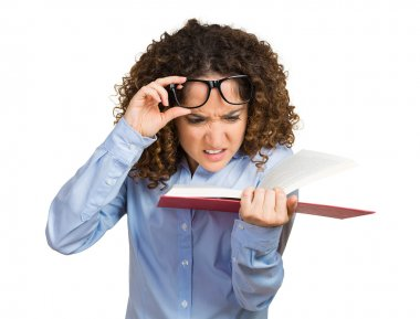 Young woman with eye glasses trying read book, having difficulties seeing text