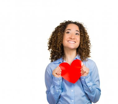 Happy smiling pretty woman looking at you camera holding red heart