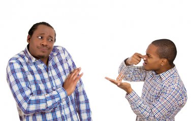 Man looking at guy, accusing, pointing at him covering nose