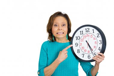 Senior woman holding clock looking anxiously pressured by lack of time