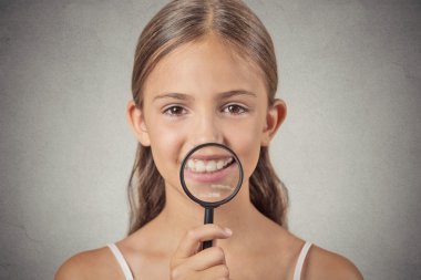 girl showing teeth through a magnifying glass