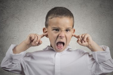 angry pissed off boy plugs his ears with fingers