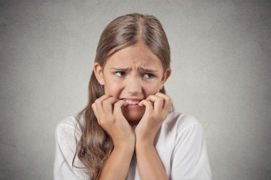 Closeup portrait nervous anxious stressed teenager girl biting fingernails looking anxiously craving something afraid has panic attack isolated grey wall background. Negative emotion facial expression stock vector