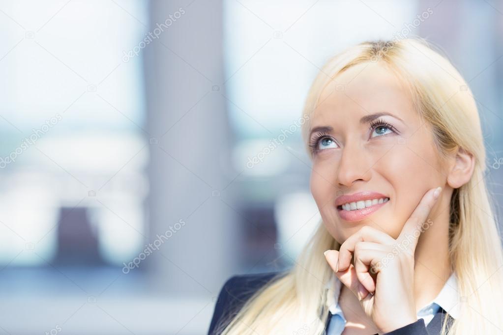 Happy woman looking upwards daydreaming