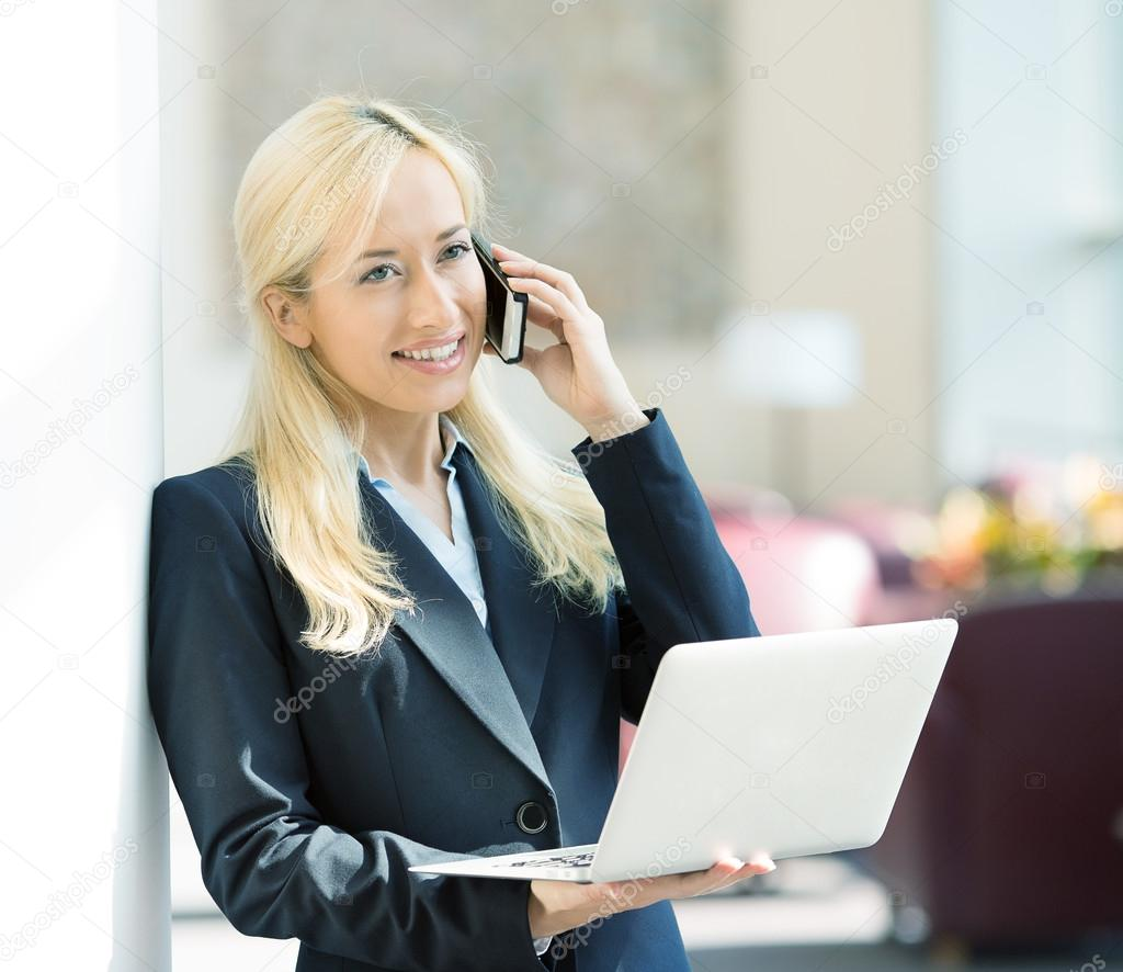 Businesswoman working on computer calling on phone