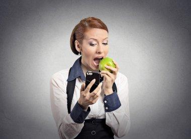 Woman looking at smart phone eating apple
