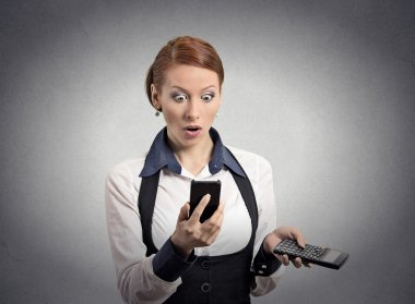Shocked woman looking on smart phone holding calculator