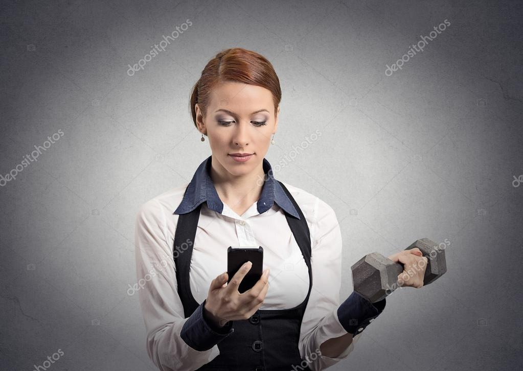 Woman reading news on smartphone lifting dumbbell