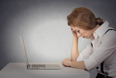 Depressed woman in front of laptop