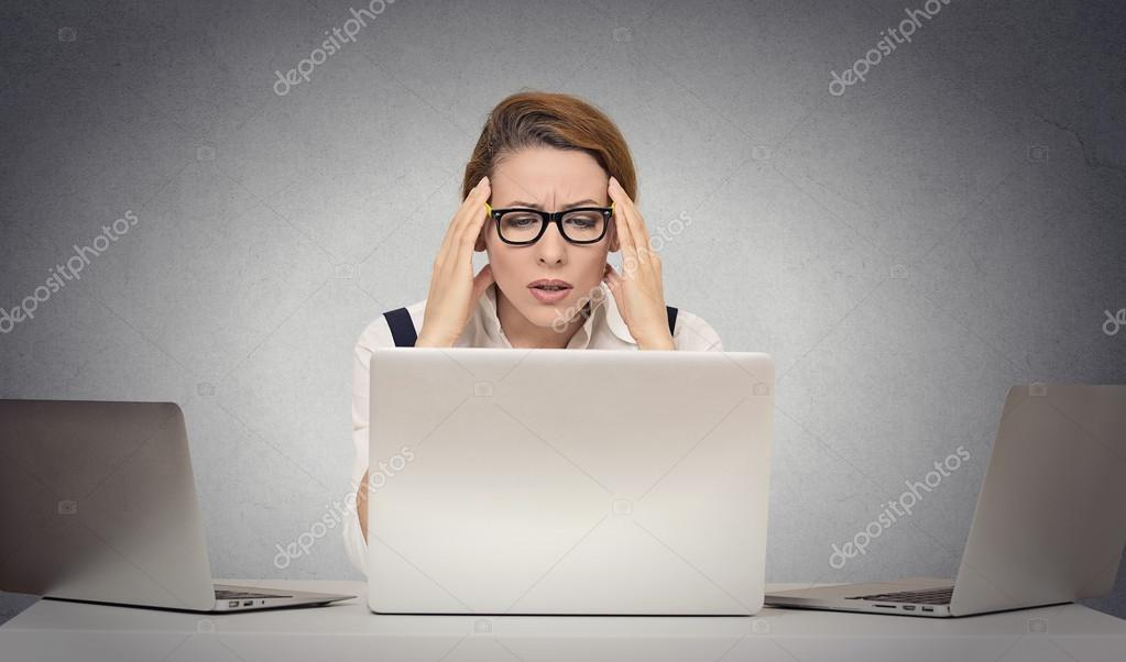 Depressed tired woman siting at desk in front of laptop
