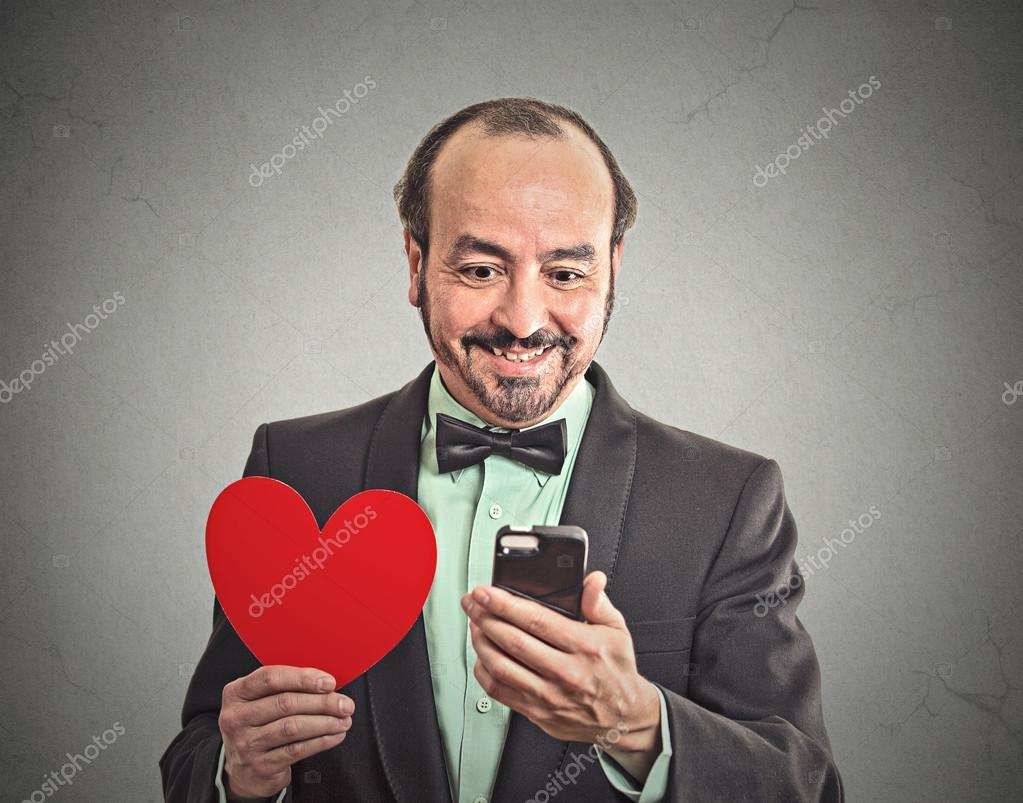 Man checking his smart phone, holding red heart