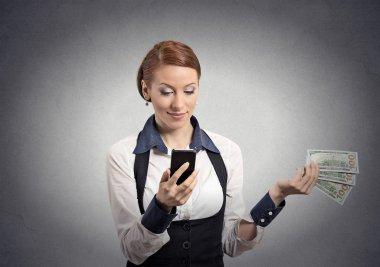 Woman looking at smartphone throwing away cash dollar bills