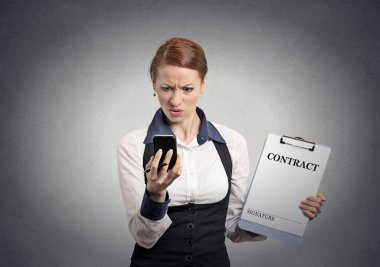 Skeptical businesswoman holding contract looking on smartphone