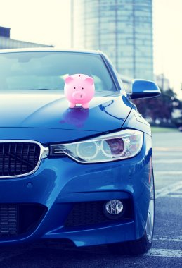 car with piggy bank on hood