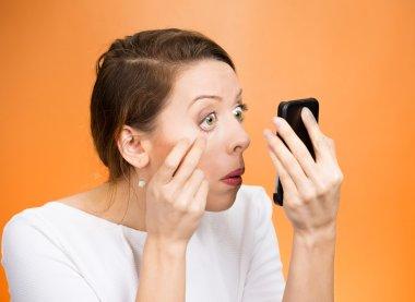 woman pulling down eyelid checking her eye