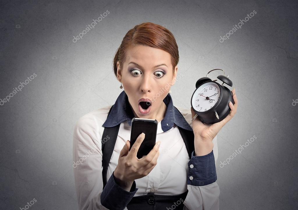 Shocked business woman with alarm clock looking at smart phone