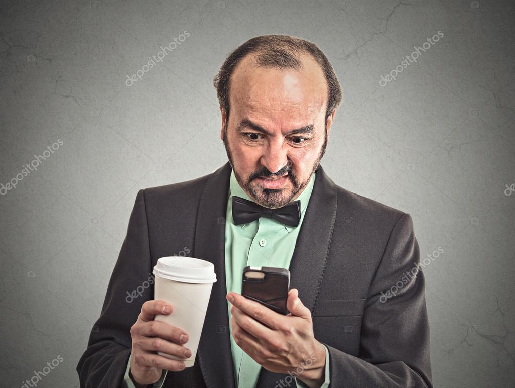 Man reading bad news on smartphone drinking coffee