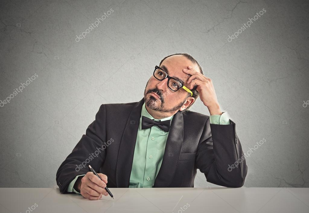Teacher sitting at table scratching his head thinking