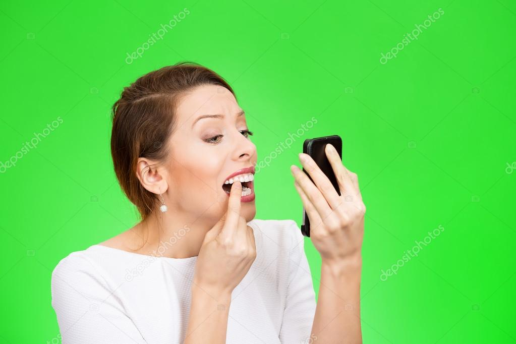 Woman looking in a mirror checking her teeth