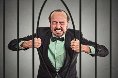 businessman bending bars of his prison
