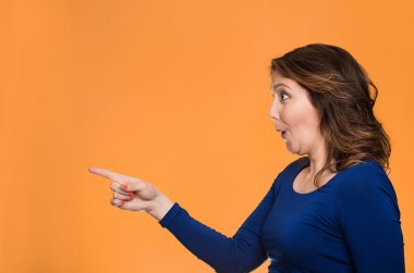 Surprised female pointing out at copy space