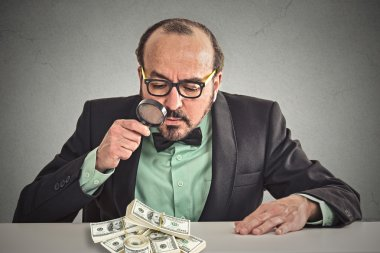 Business man looking through magnifying glass on stack of dollar banknotes