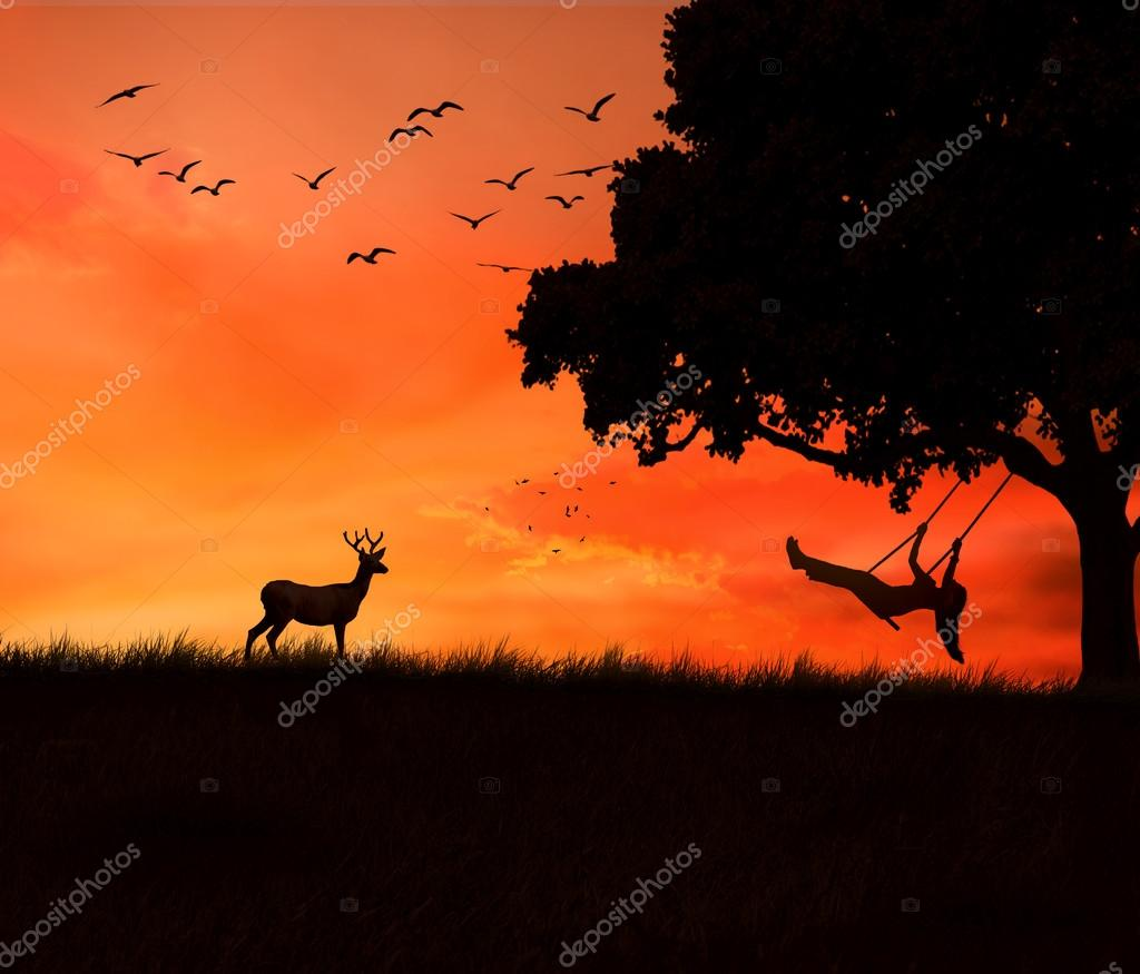 woman on a swing of tree isolated on sunset evening dusk sky background.