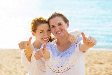 Joyful women mother daughter showing thumbs up having fun vacation on beach