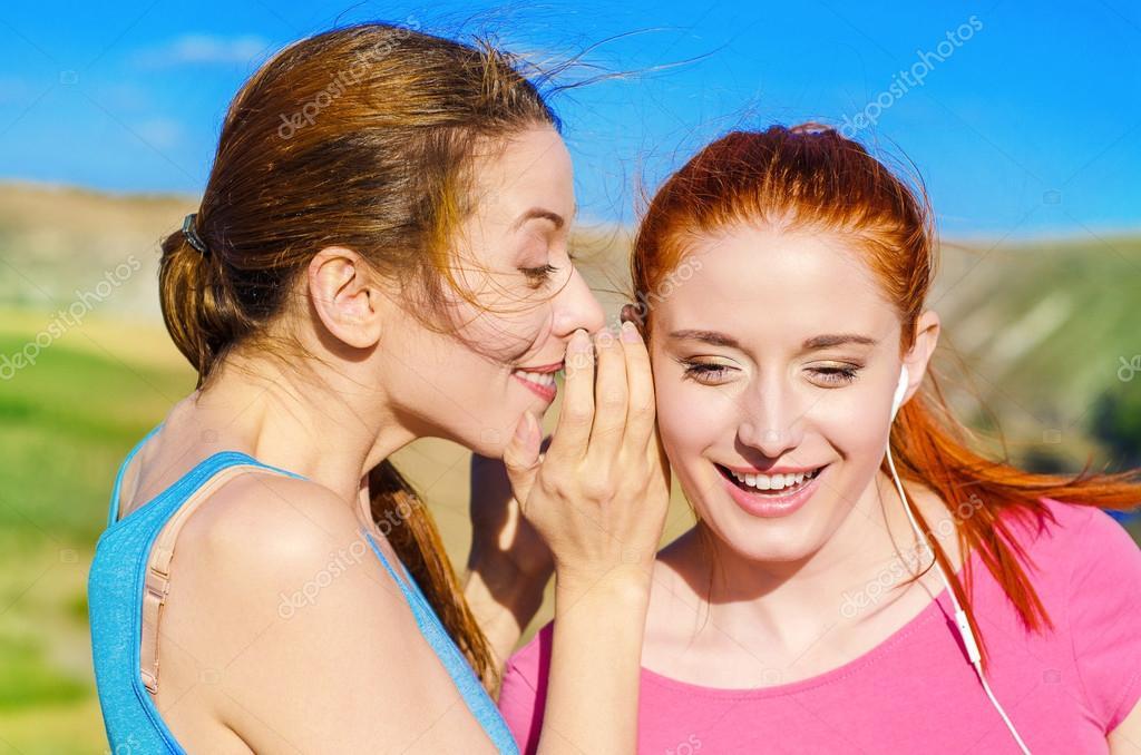 Girl whispering into woman ear telling her something secret latest gossip