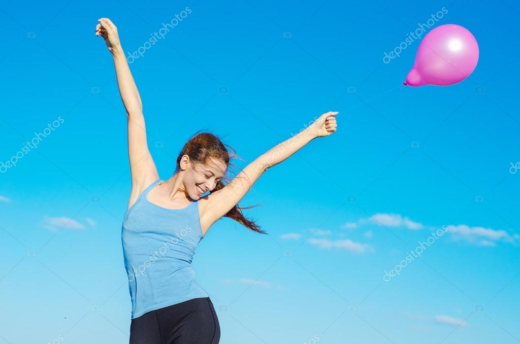 happy smiling woman arms raised holding pink flying air balloon