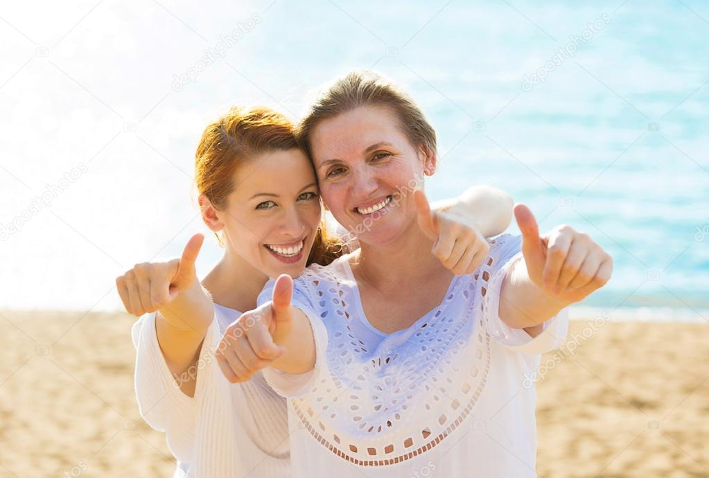 Joyful women mother daughter showing thumbs up having fun vacation on beach