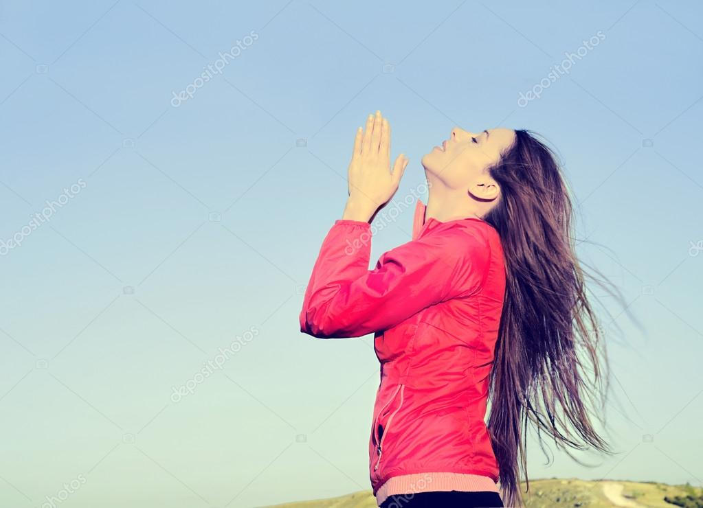Woman arms raised up to blue sky praying thankful for freedom