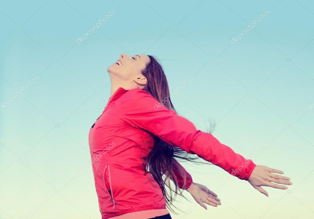 Woman smiling arms raised looking at blue sky taking deep breath freedom